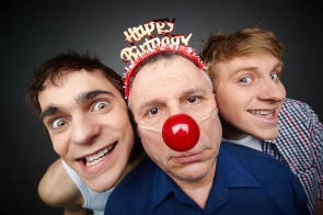 Two guys having fun playing pranks on a senior man celebrating birthday or fool's day