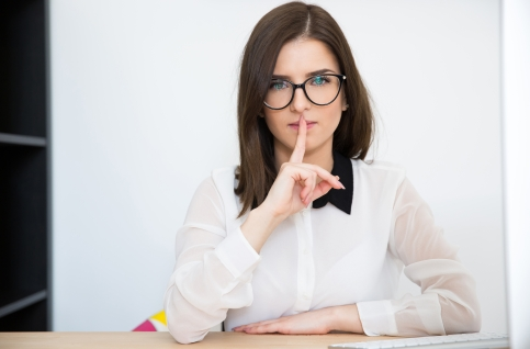 Young businesswoman sitting at the table with finger over lips