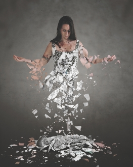 A woman shatters into hundreds of pieces of glass.