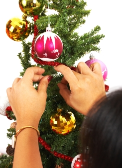 Decorating The Christmas Tree With Colored Balls And Tinsel