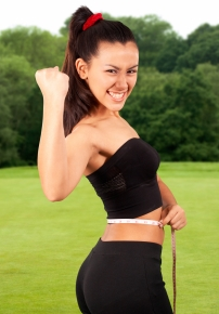 Healthy Girl Exercising And Checking Her Waistline Outside