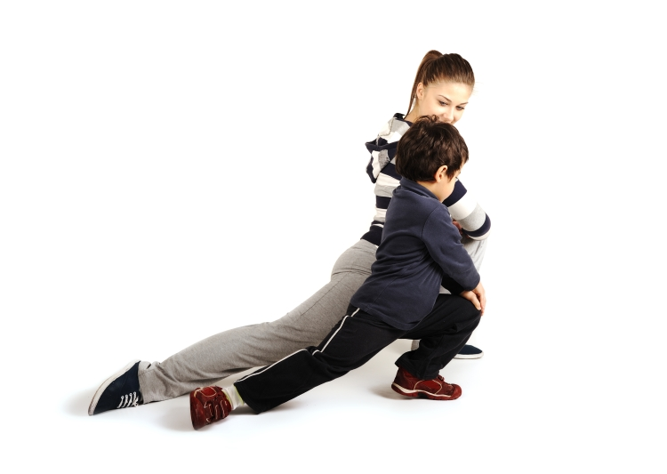Family - young woman and kid - doing fitness exercises indoors