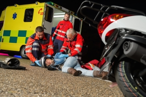 Paramedics helping injured motorcycle driver