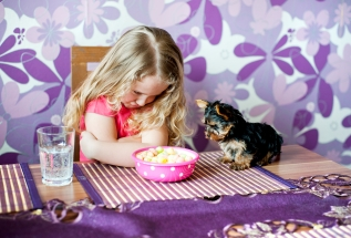 Little girl is playing with her little puppy