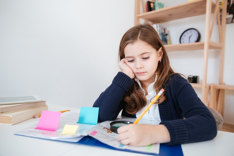 graphicstock-serious-little-girl-sitting-and-writing-at-the-table-in-classroom_SdMJHaiL3e.jpg
