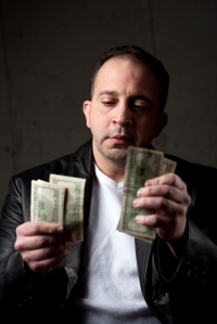 A-middle-aged-man-counting-a-handful-of-one-hundred-dollar-bills-shallow-depth-of-field-crop