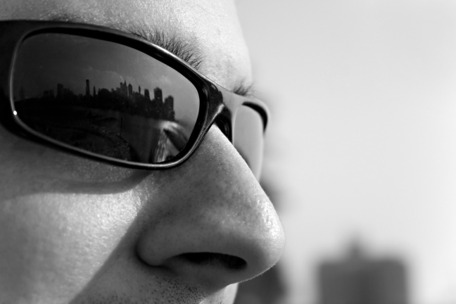 Close-up-of-a-man-wearing-sunglasses-with-the-new-york-city-skyline-reflectin crop