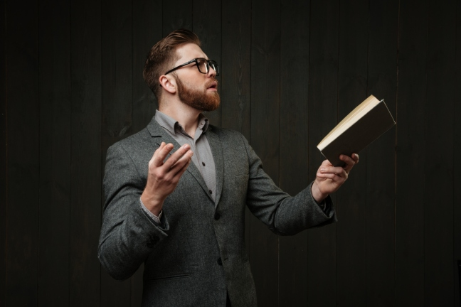 graphicstock-bearded-young-man-in-eyeglasses-and-casual-suit-reading-book-and-gesturing-with-hands-isolated-on-the-black-wooden-background_HU1lvTu7d3x crop