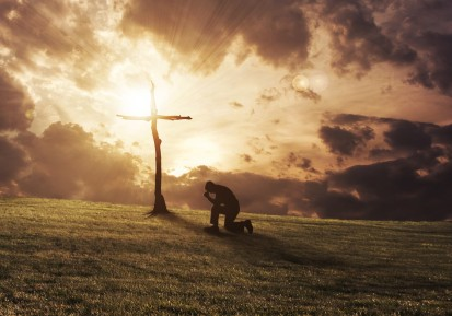 a-man-kneeling-at-a-cross-at-sunset cropped