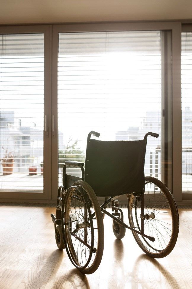 graphicstock-empty-wheelchair-in-sunny-living-room-next-to-the-couch_B_eEySuUzZ