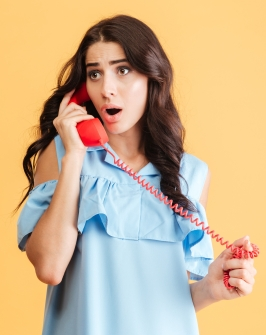 graphicstock-shocked-astonished-beautiful-woman-in-blue-dress-talking-on-red-telephone-isolated-on-a-orange-background_S_E7Rscr2l