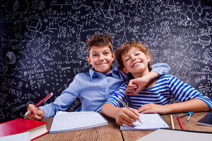 graphicstock-young-school-boy-and-girl-sitting-at-the-desk-doing-their-homework-against-big-blackboard-with-formulas-and-mathematical-sym