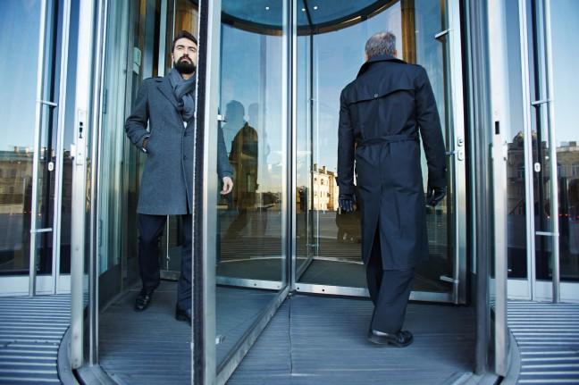 storyblocks-revolving-door-with-elegant-businessmen-inside_r8xjrjHDC-