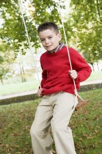 young-boy-playing-oon-tree-swing-in-garden_StNg24ZCrs