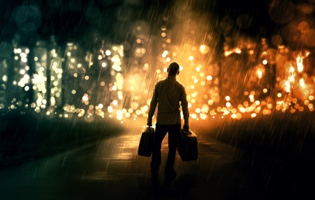 a-man-walking-down-an-empty-road-with-two-suitcases-towards-the-city_SX-YzkGx0