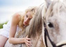graphicstock-woman-in-white-dress-walking-with-horse-in-green-countryside_S0rnARoZb